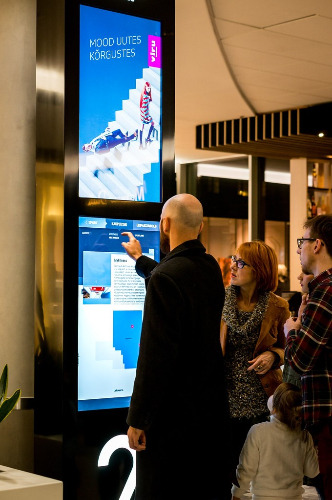 A man using an interactive digital signage screen in a mall